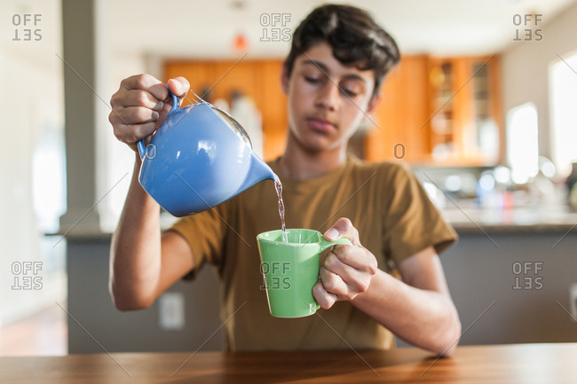 Teenage boy pouring cup of tea in house alone
