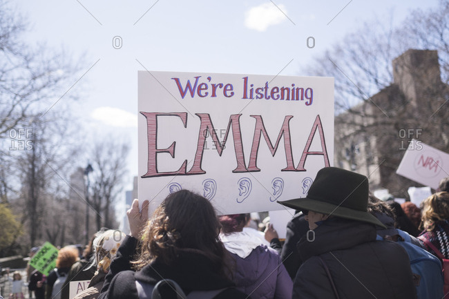 New York, NY - March 24, 2018: Back view of large crowd of protestors holding banners in the air