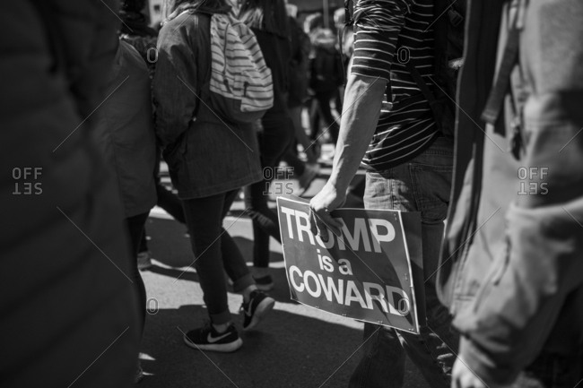 New York, NY - March 24, 2018: Civilian holding anti President Trump sign low in crowd of marchers
