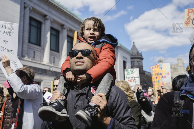New York, NY - March 24, 2018: Father holding small child on shoulders at social justice protest