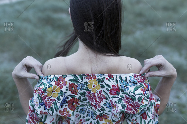 Unrecognizable young woman with her back towards camera wearing flowery dress on green field