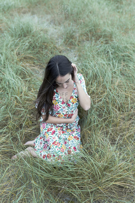 Close up portrait of young brunette sitting on grass with flowery dress