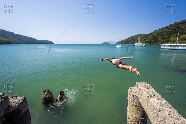 August 30, 2017: Man diving into water at Palmas Beach in Ilha Grande, Rio de Janeiro, Brazil