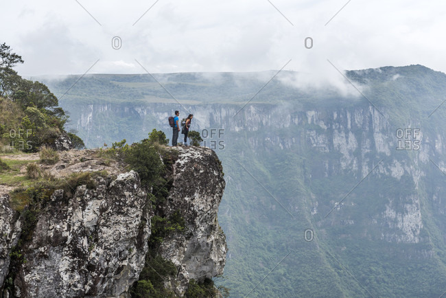 Couple hiking on edge of rock in Canion Fortaleza, Cambara do Sul, Rio Grande do Sul, Brazil