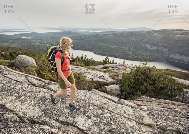An active woman takes in in the view of the Atlantic Ocean from the summit of Pemetic Mountain while hiking in Maine's Acadia National Park.