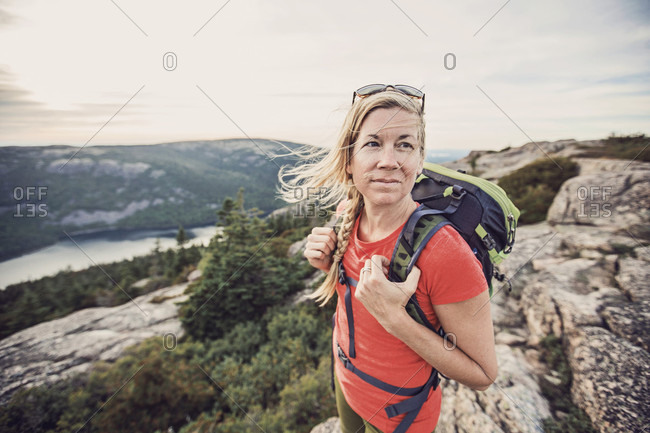 An active woman takes in in the view of the Atlantic Ocean from the summit of Pemetic Mountain in Maine's Acadia National Park.