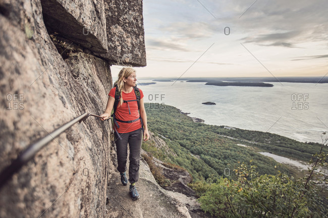 An active woman walks along a precipitous cliff on the Precipice Trail in Maine's Acadia National Park.