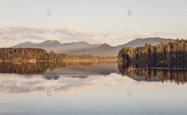 The late afternoon light catches the calm waters of Flagstaff Lake and Bigelow Mountain in the distance.