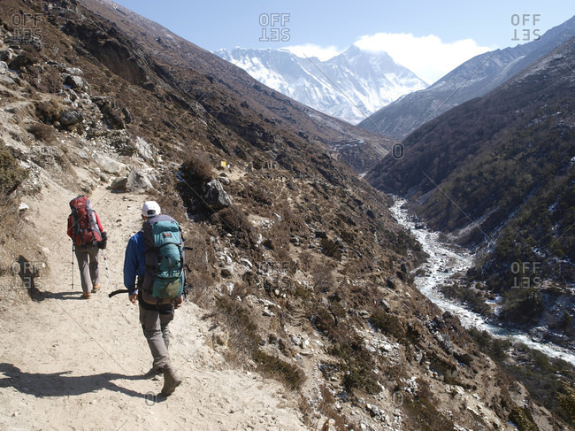 March 30, 2008: Two hikers on trail of Khumbu valley, just after Namche Bazar, with summit of Mount Everest in background, Nepal