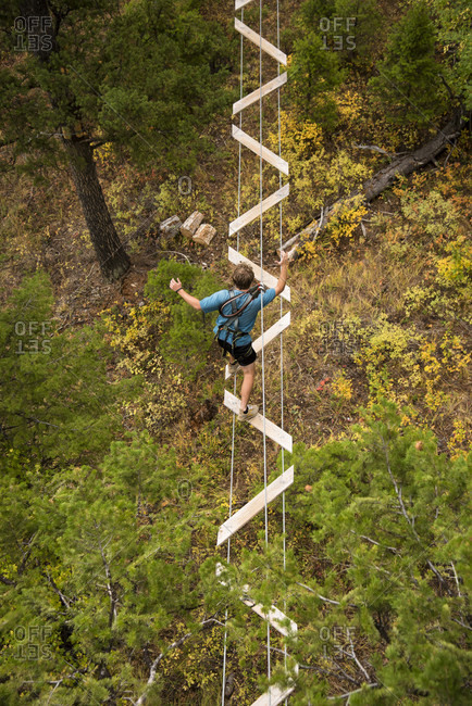 September 18, 2016: View from above of young man in his twenties on treetop rope obstacle course in rope park, Jackson, Wyoming, USA