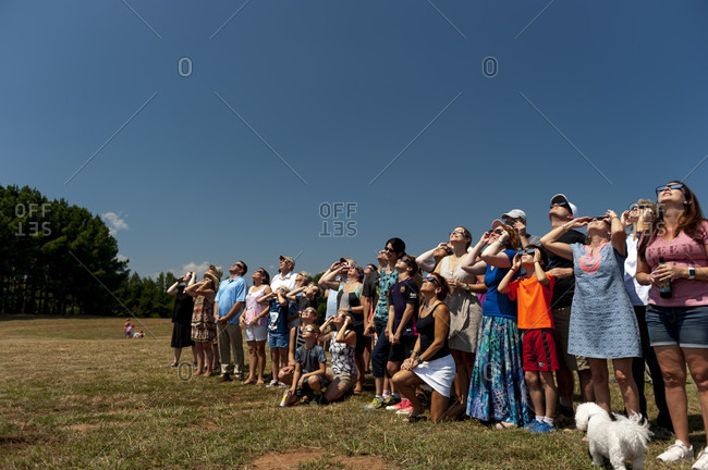 August 21, 2017: Large group of people wearing dark glasses, standing together and watching eclipse of Sun, Woodruff, South Carolina, USA