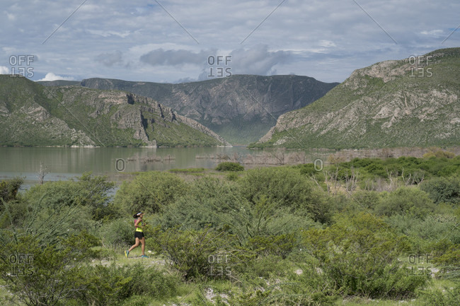 August 19, 2017: Young woman hiking on rocky trail in area of Presa Zarco in Durango, Mexico