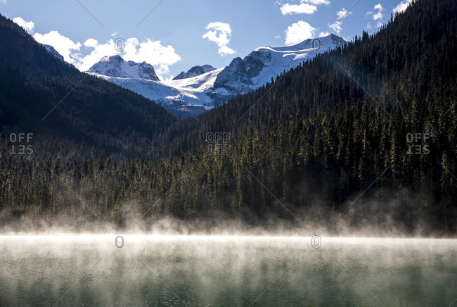 Fog rises off Lower Joffre Lake early in the morning and distant mountains can be seen covered in glaciers. This hike is a popular one with in the Duffy Lake Provincial Park due to its stunning views and ease of access. Pembreton, British Columbia, Canada