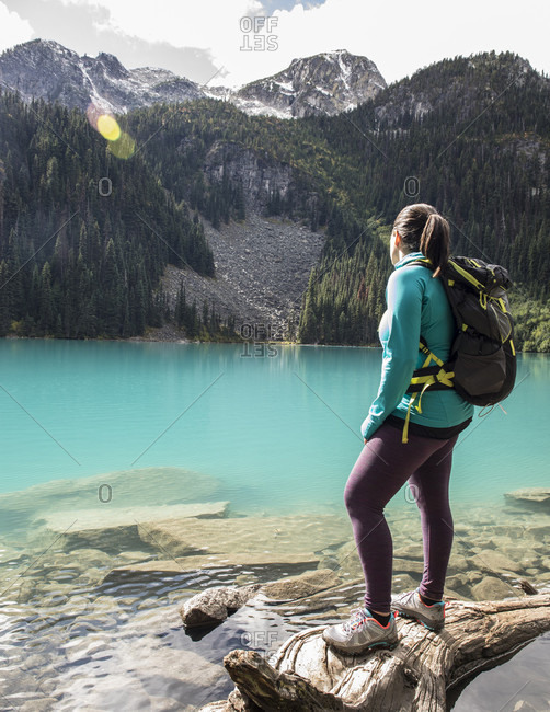 A women stands on a fallen tree next to Middle Joffre Lake and stares out at the surrounding peaks. The lake is a vibrant turquoise color due to glacier till. This hike is a popular one with in the Duffy Lake Provincial Park due to its stunning views and