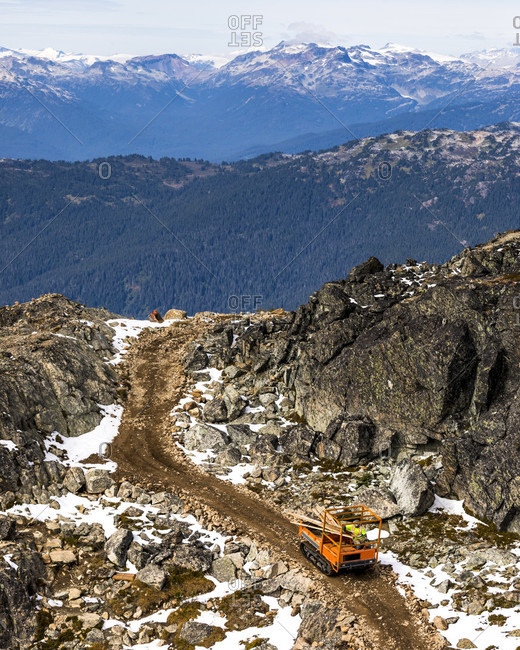 A small rock crawler machine carries wood down a rocky incline in the alpine, while working to build a suspension bridge at the peak of Whistler Mountain in British Columbia, Canada