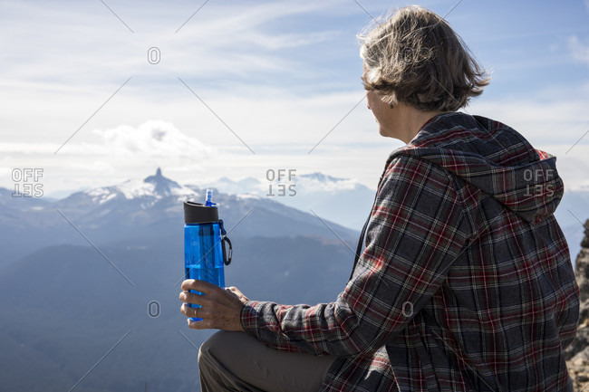 Female hiker resting and drinking water at top of Whistler Mountain, Black Tusk in background, Garibaldi Provincial Park, Whistler, British Columbia, Canada