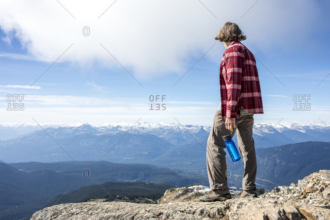 Hiker resting and looking at view while standing at top of Whistler Mountain, Garibaldi Provincial Park, Whistler, British Columbia, Canada