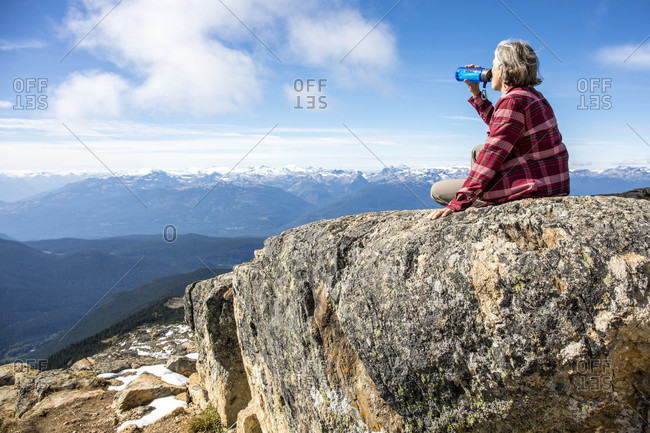 Female hiker resting and drinking water at top of Whistler Mountain, Garibaldi Provincial Park, Whistler, British Columbia, Canada