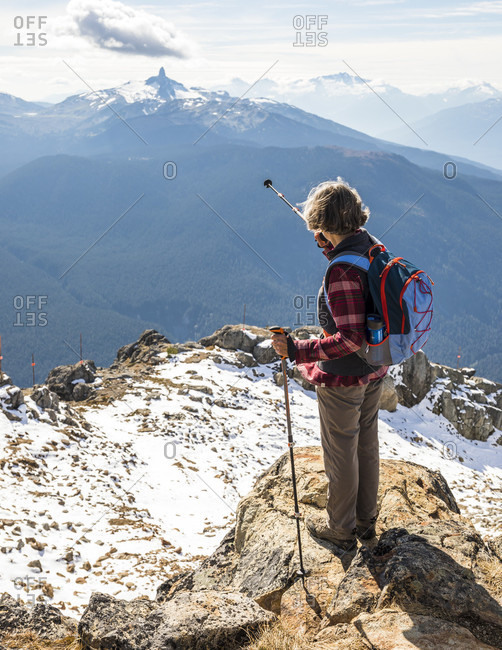 Female hiker pointing at Black Tusk mountain from top of Whistler Mountain, Garibaldi Provincial Park, Whistler, British Columbia, Canada