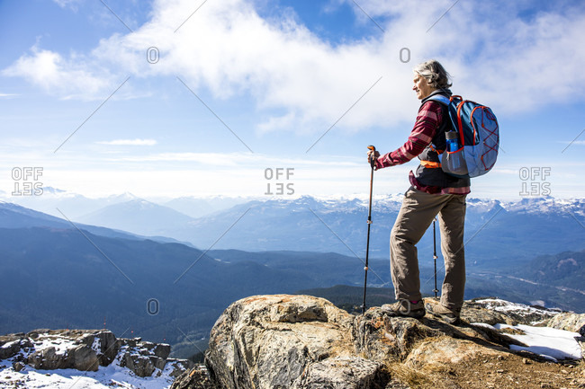 Female hiker looking at view of Garibaldi Provincial Park from top of Whistler Mountain, Whistler, British Columbia, Canada