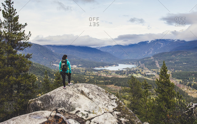 A women takes in the view of Whistler and Green lake from a lookout along the Flank Trail. This trail is part of the extensive network of trails that surround Whistler, British Columbia, Canada