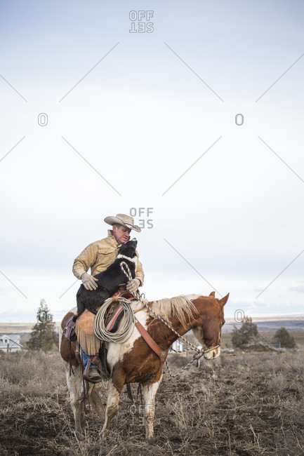 February 22, 2017: Clear sky over rancher horseback riding with pet dog, Oregon, USA