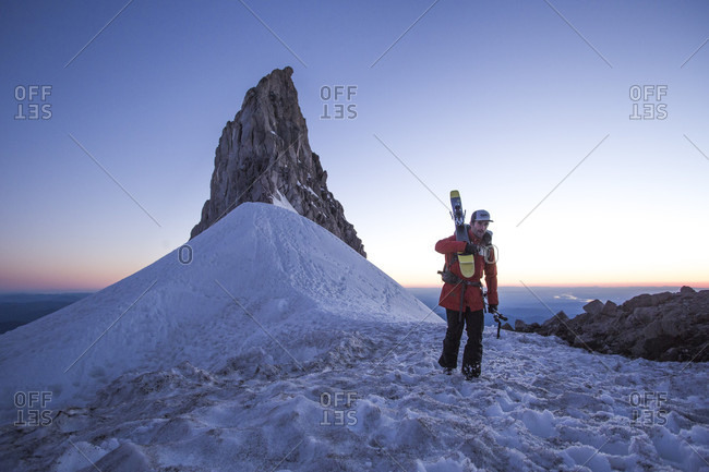 June 23, 2017: Skier carrying skis on snowy mountain with Sun setting in background, Mount Hood, Oregon, USA