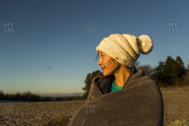 December 2, 2014: Young woman sitting in knit hat and wrapped in blanket while resting after running in Discovery Park, Seattle, Washington Sate, USA