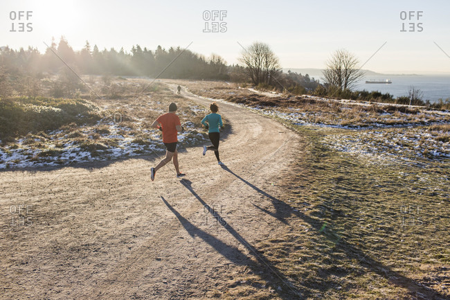 December 2, 2014: Man and woman jogging on dirt road in winter, Discovery Park, Seattle, Washington State, USA