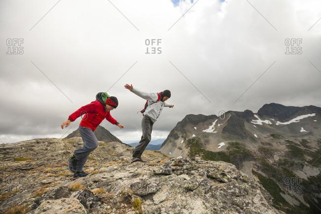 Two hikers battling strong wind on rocky ridge, Merritt, British Columbia, Canada