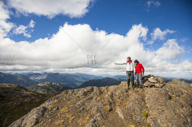 Father pointing out familiar landmarks to son from summit of mountain, Merritt, British Columbia, Canada