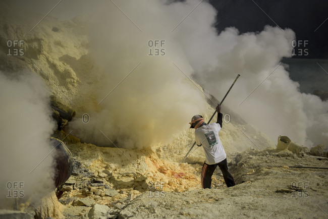 June 13, 2015: Miner extracting sulfur rocks from Kawah Ijen Volcano, East Java, Indonesia