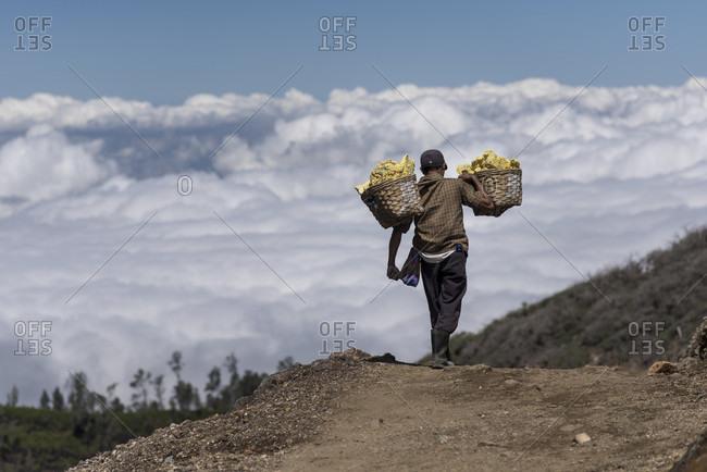 June 11, 2015: Sulfur miner descending from Kawah Ijen carrying basket full of sulfur rocks, Kawah Ijen, Indonesia
