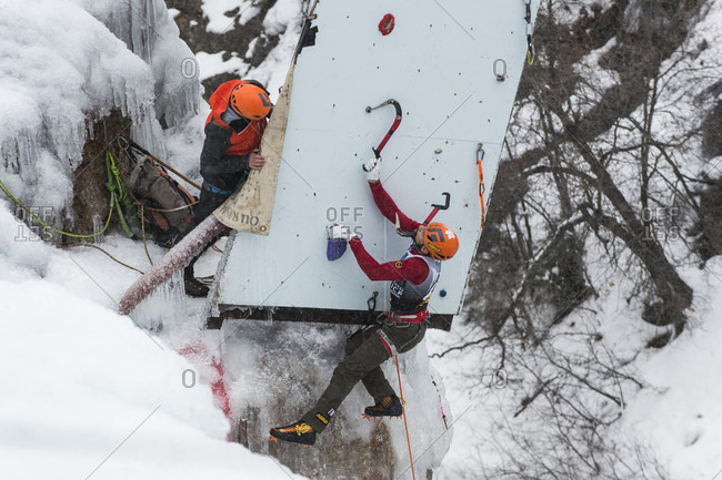 January 21, 2017: Male ice climber hooking ice axe onto hold near top of competition route, Ouray Ice Park, Colorado, USA