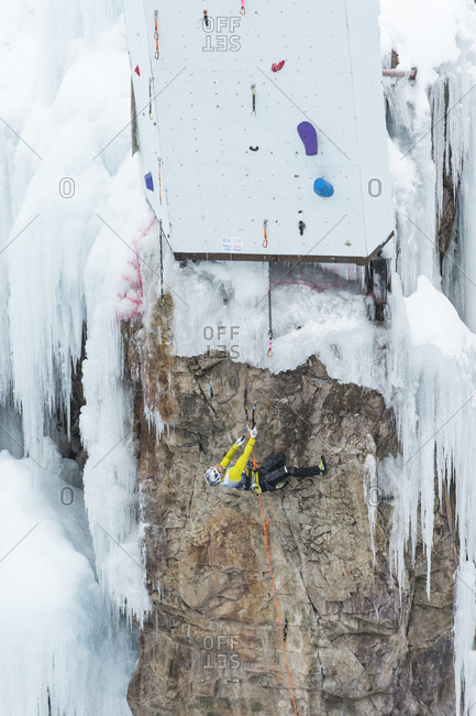 January 21, 2017: Male ice climber clinging horizontally to rocks on competition route, Ouray Ice Park, Colorado, USA