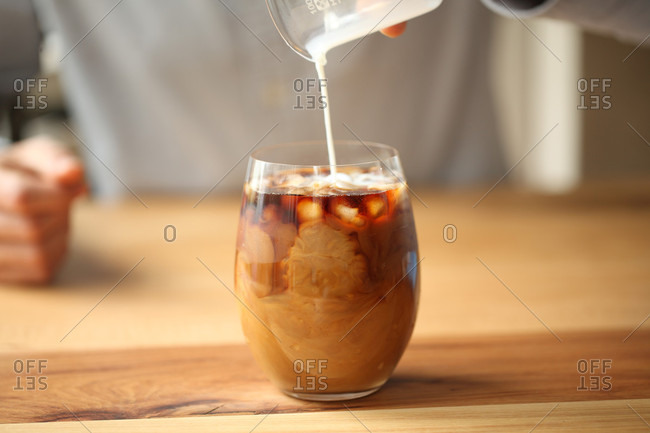 Close up of pouring milk to glass with coffee, Oakland, USA