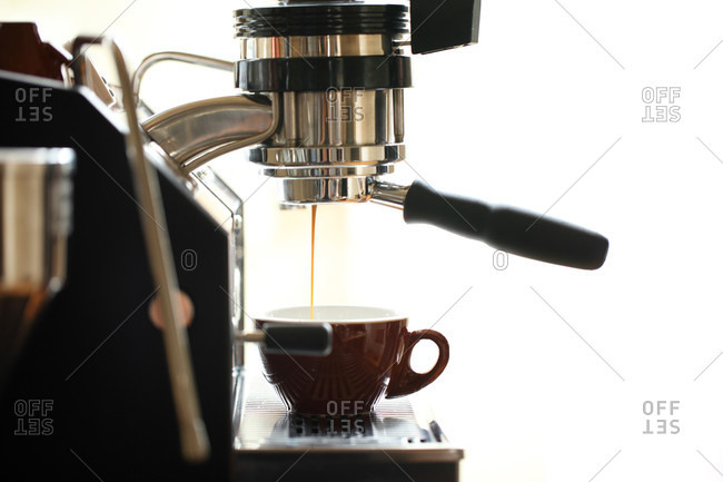 Profile view of an espresso machine pulling a shot