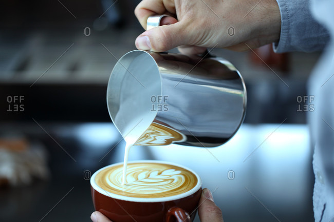 Close up of pouring milk into brown cup with coffee, Oakland, USA