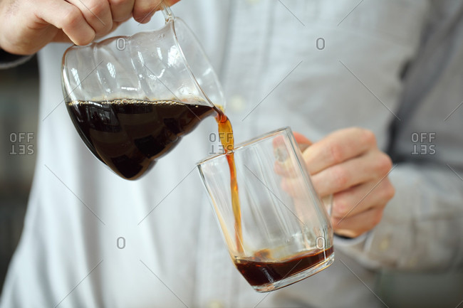 Hands of barista pouring coffee into glass mug, Oakland, California, USA