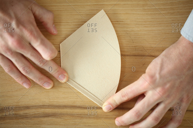 Close up of hands of person holding coffee filter, Oakland, California, USA