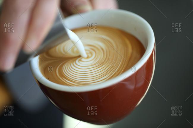 Close up of barista pouring milk into cappuccino, Oakland, California, USA