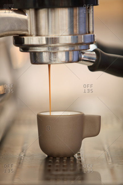 Espresso coffee pouring from coffee maker into cup, Oakland, California, USA