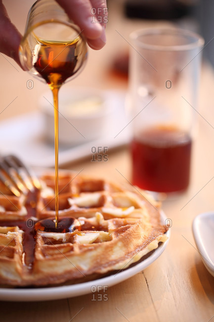 Person pouring honey over waffles, Chelsea, Manhattan, New York City, USA
