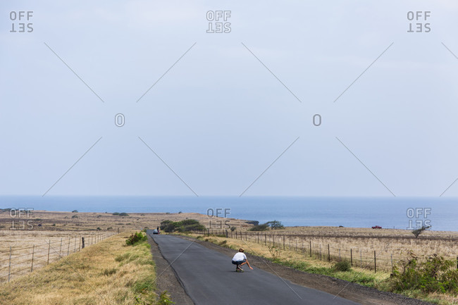 A man skateboards down the road towards Ka Lae, also known as South Point, the southernmost point of the Big Island of Hawaii and of the United States. People come to fish, jump off cliffs, and explore rock formations.