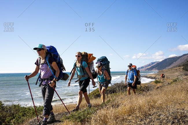 Backpackers hiking along coastline, Lost Coast Trail, Kings Range National Conservation Area, California, USA