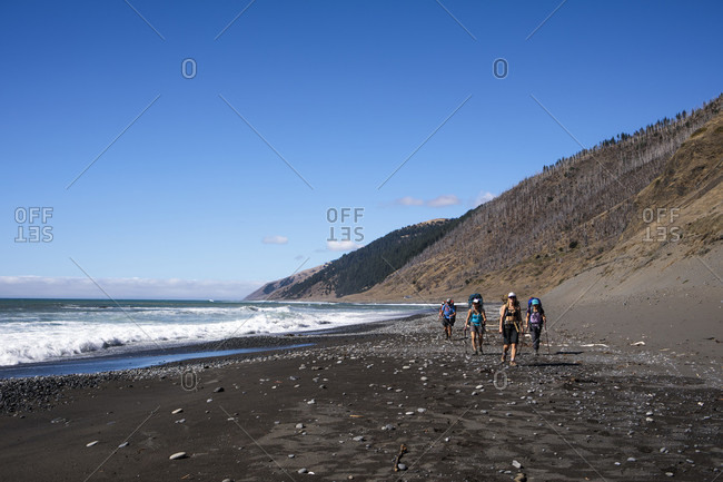 Backpackers hiking along beach, Lost Coast Trail, Kings Range National Conservation Area, California, USA