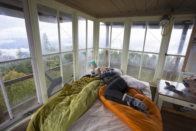 November 16, 2017: Woman relaxing with phone on bed inside Pickett Butte Fire Lookout near Tiller Oregon, USA