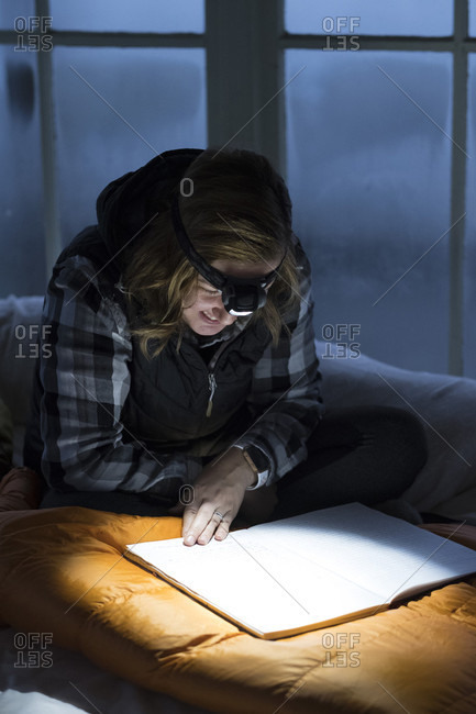 Woman reading guest log at twilight with headlamp on inside Pickett Butte Fire Lookout near Tiller, Oregon, USA