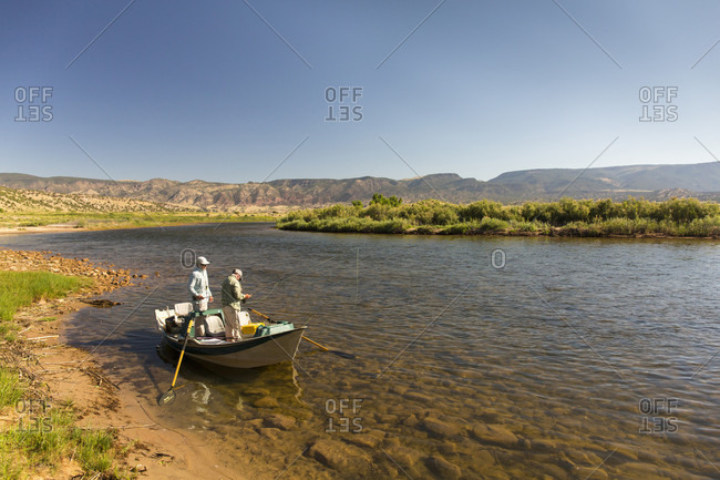 July 27, 2016: Two men fly fishing in rowboat on bank of Green River, Dutch John, Utah, USA