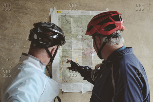 September 17, 2016: Two middle-aged cyclists checking map, Pamplona, Navarre, Spain